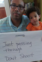 """Photo of Chris Lebron holding sign """"Don't Shoot"""""""